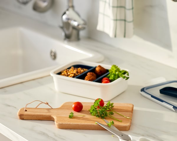 سطح عمل مطبخ مع وجبة مقسمة في حجيرات صندوق غداء، ولوح تقطيع مع طماطم وأعشاب طازجة.
