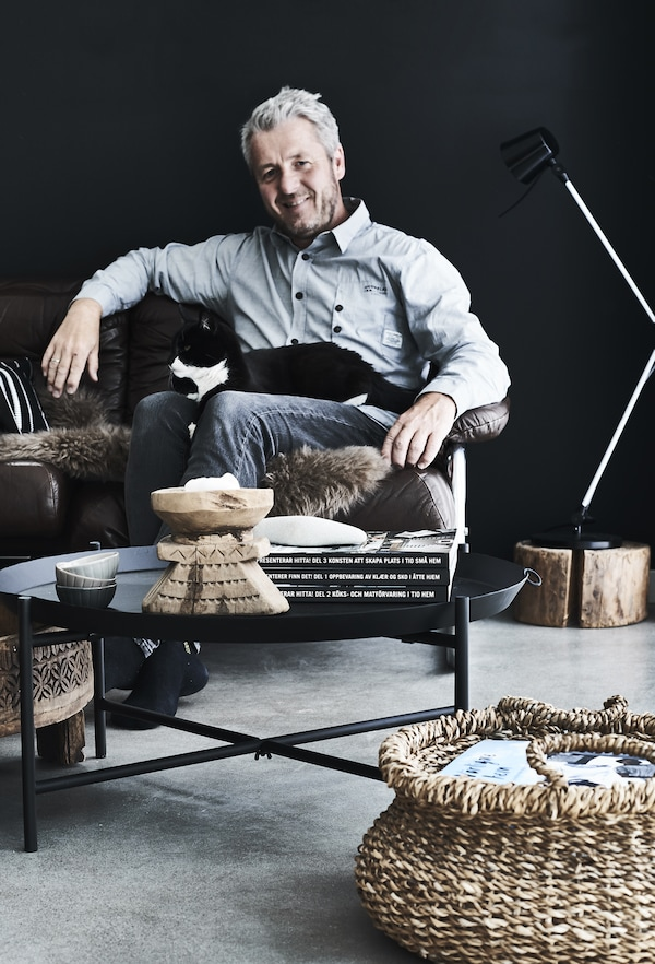 Stig sitting in a leather sofa with a black and white cat on his lap.