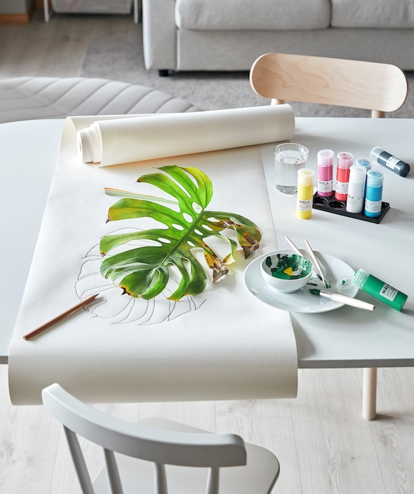 Стіл у вітальні облаштований для уроку мистецтва з рослинними елементами: MÅLA МОЛА фарби, папір для малювання та частково висохле листя монстери.