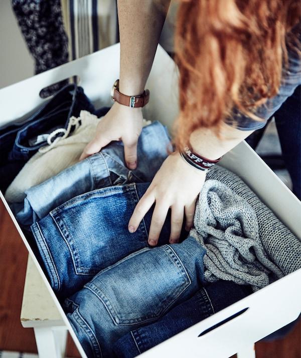 Stine en train de ranger un jeans plié dans une boîte blanche.