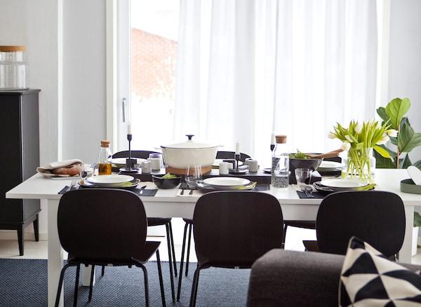 Sto i stolice za šestoro, s monohromatskim posuđem i zelenilom.