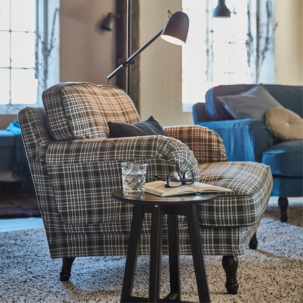 STOCKSUND armchair in SEGERSTA multicolour cover with a small table holding a glass, book and spectacles, plus a lamp behind.