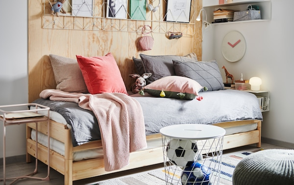 Stohovatelná postel UTÅKER se spoustou polštářů a dalších textilií, vedle je noční stolek, úložný díl a dekorace.