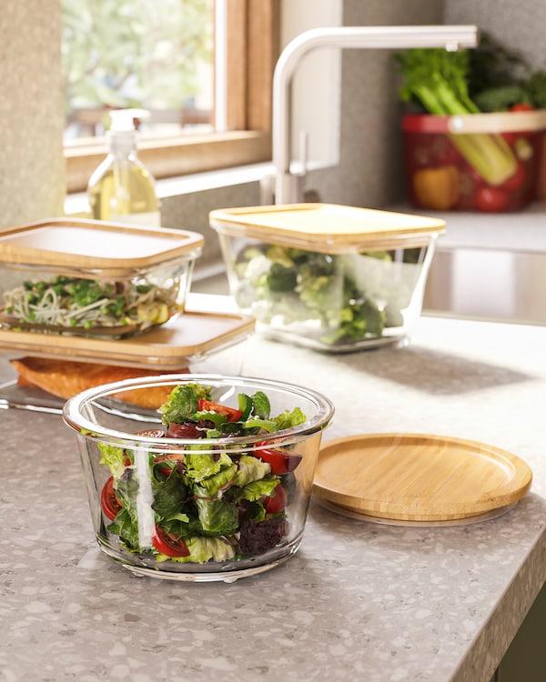 Stojące na blacie kuchennym okrągłe szklane pojemniki na żywność ze szczelnie dopasowanymi bambusowymi pokrywkami i warzywami w środku.