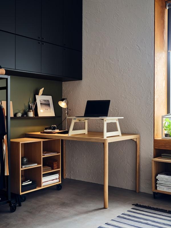 Stół i regał na kółkach RÅVAROR ustawione tak, aby tworzyły miejsce do pracy. Na stole stoi laptop.