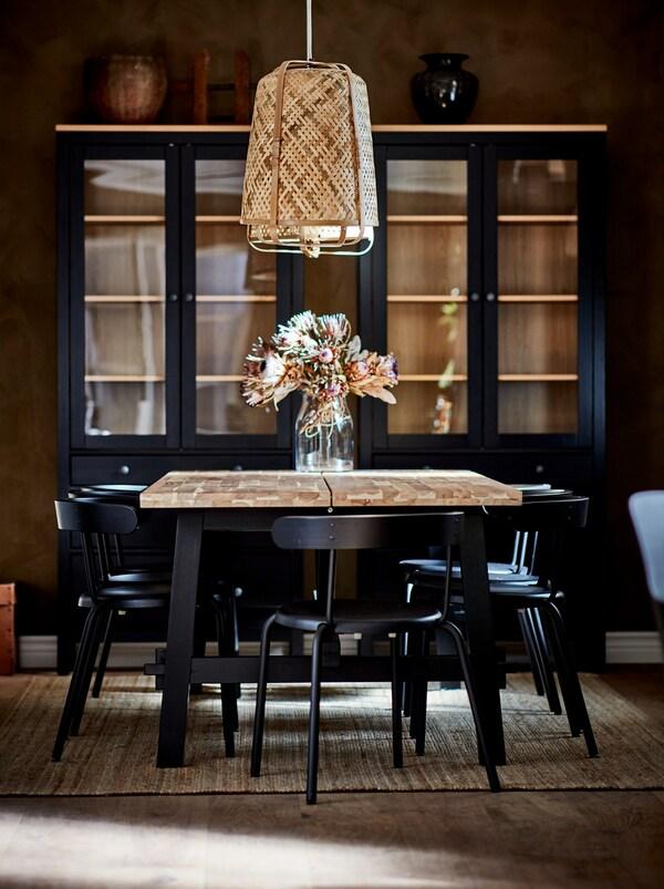 Stół jadalniany SKOGSTA z kwiatami w wazonie pod lampą wiszącą KNIXHULT, otoczony ciemnymi krzesłami. Pod ścianą w tle widoczne są dwie ciemne witryny.
