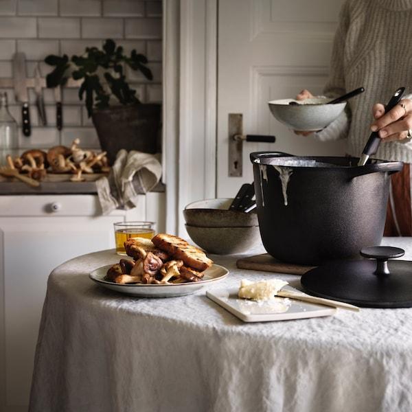 Stoł kuchenny przykryty obrusem z grnkiem z serii VARDAGEN.