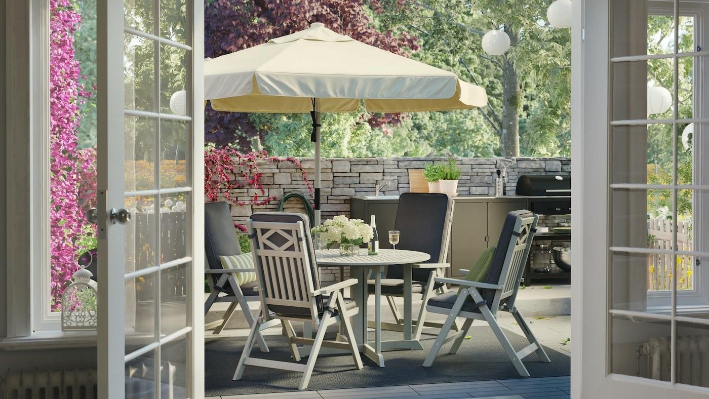 Stół ogrodowy z beżowym parasolem, rozkładane fotele z ciemnoszarymi poduszkami, ceglany mur i stanowisko do grillowania.
