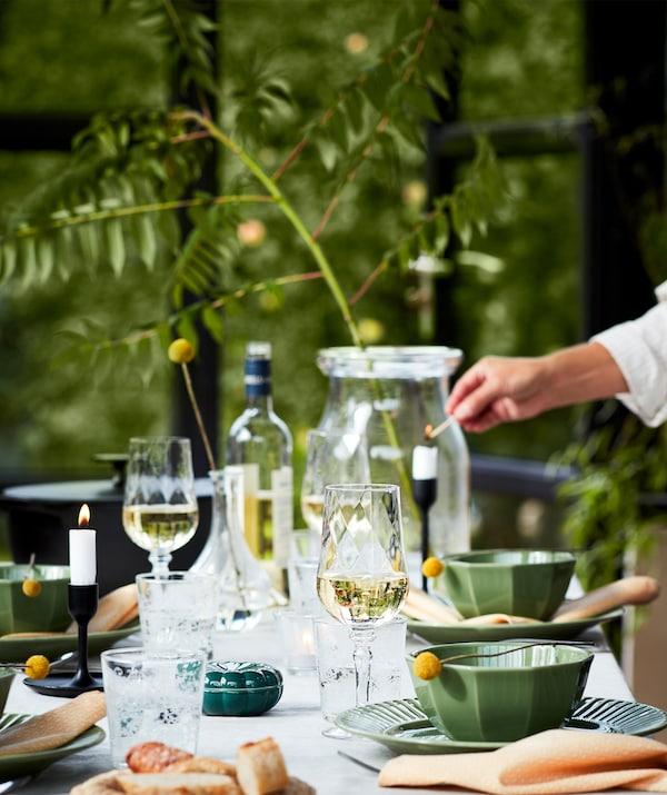 Stôl prestretý vonku na večeru so zelenými taniermi, vínovými pohármi, sviečkami a ďalšími vecami.