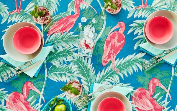 Stôl s obrusom s farebným tropickým vzorom v ružovej, zelenej a modrej farbe. Stôl je prestretý riadom v ladiacich farbách.