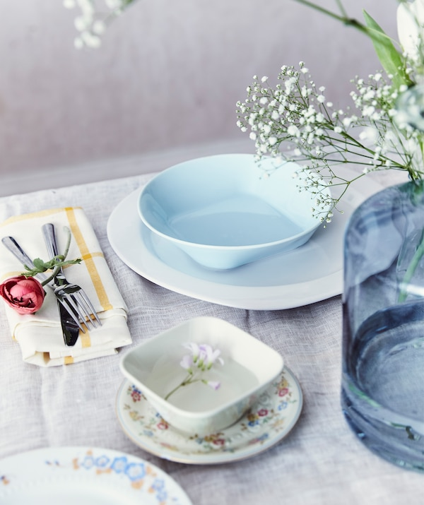 Стол, сервированный узорчатой посудой в пастельных тонах и большой голубой вазой с цветами на белой скатерти.