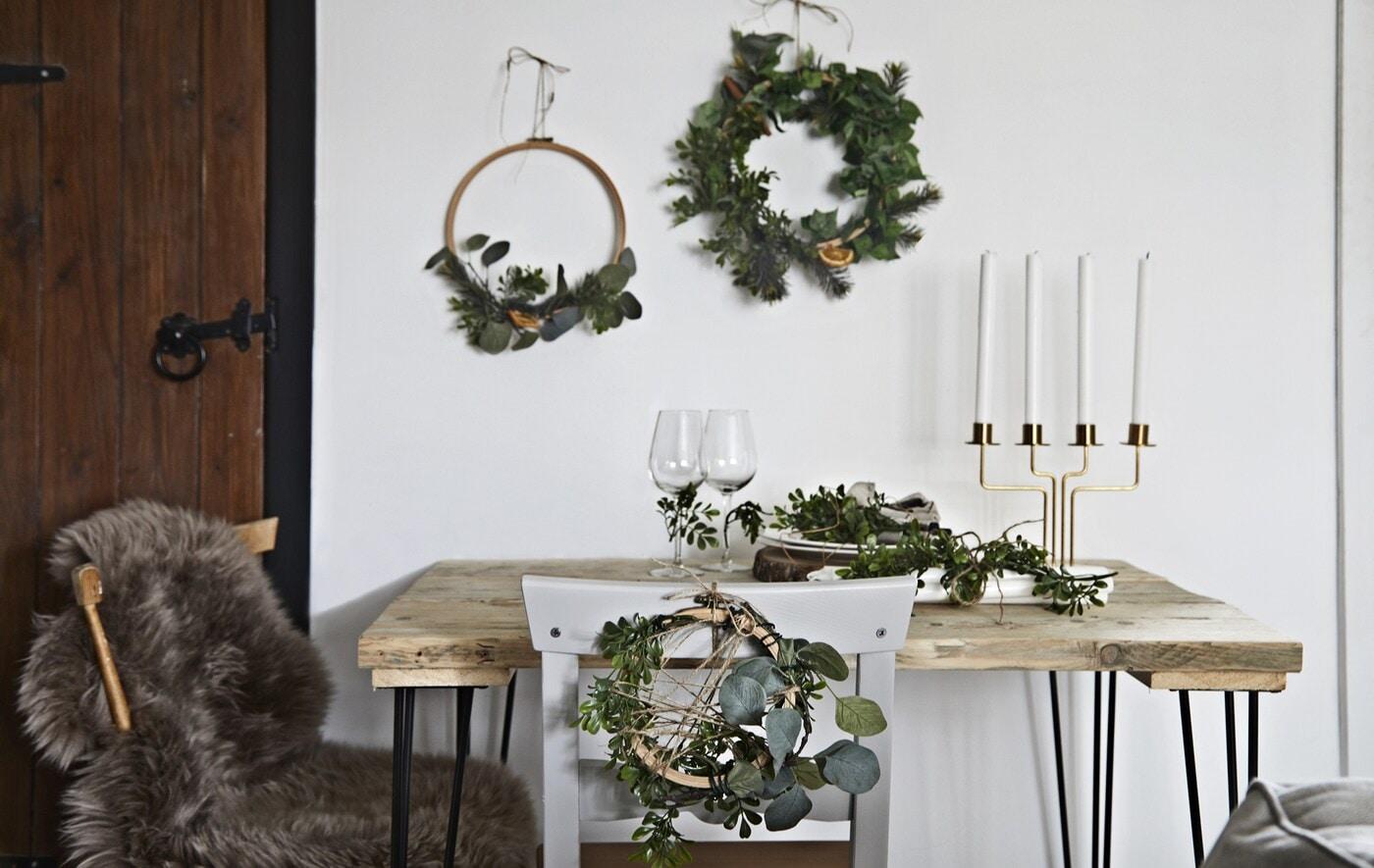 Стол, украшенный праздничными венками и аксессуарами.