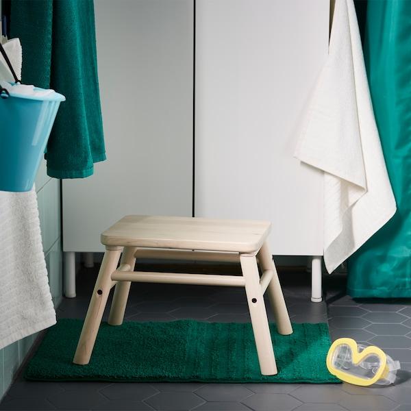 Stolička IKEA VILTO z masívnej brezy postavená pred kúpeľňou s časopismi uloženými v sivej látke.