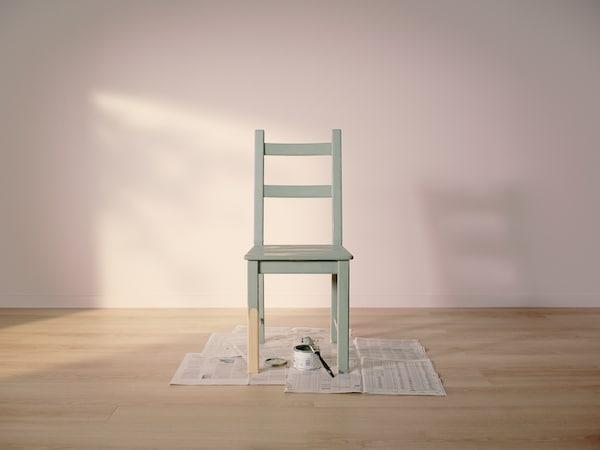 Stolička IVAR so svetlozeleným náterom stojí v prázdnej miestnosti so svetloružovými stenami na drevenej podlahe, ktorá je prikrytá starými novinami.
