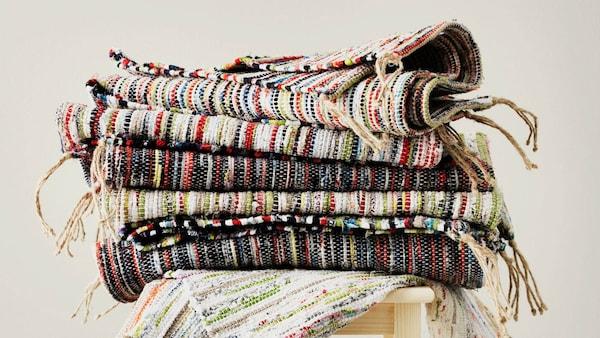 Stolička s tkanými kobercami so zvyškom látky z posteľných obliečok.