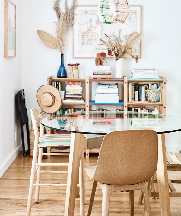 Столовая со стеклянным столом и коричневыми стульями. Возле белой стены стоит книжная полка.