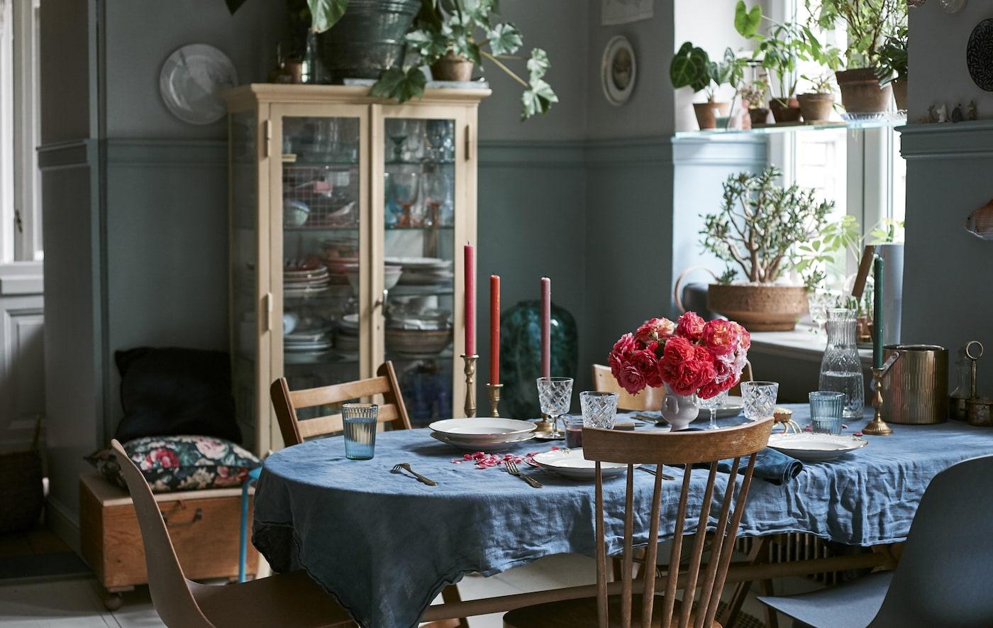 Столовая со стульями, подушками, стеклянной посудой и столовой посудой.