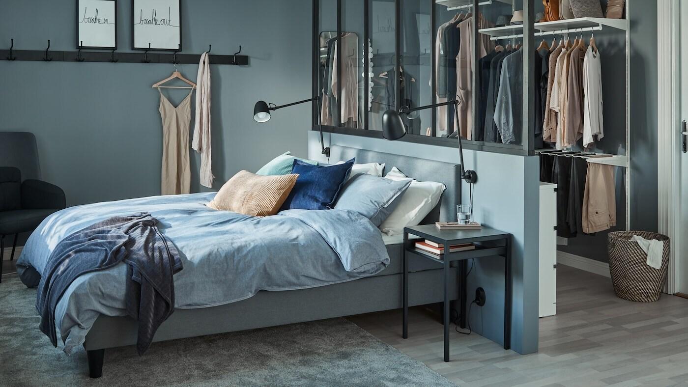 Stor grå kontinentalsäng med vadderad huvudgavel, bakom finns en rumsavdelare och walk-in closet.