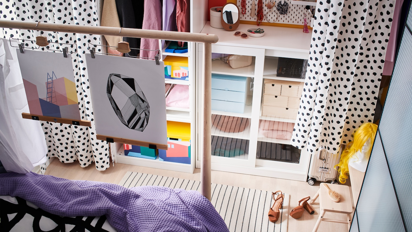 Storage along a wall, including a SYVDE cabinet with glass doors, acts as a walk-in wardrobe with curtains for doors.
