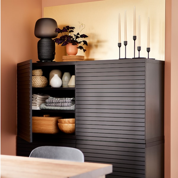 Storage behind anthracite doors, a brass-coloured wall panel, a black lamp, candles and a purple plant.