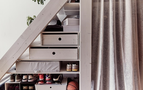 Storage boxes and shoes stored on shelves under a flight of stairs.