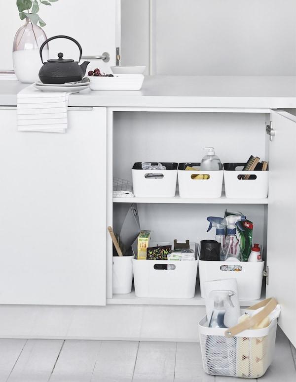 Storage boxes inside a kitchen cupboard.