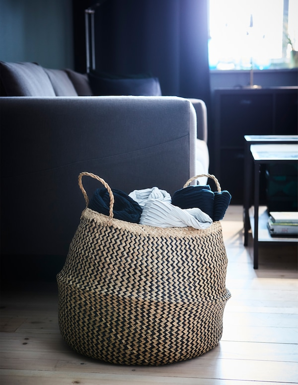 Storage isn't more than shelving and boxes. Try using a decorative basket like FLÅDIS to store your living room textiles.