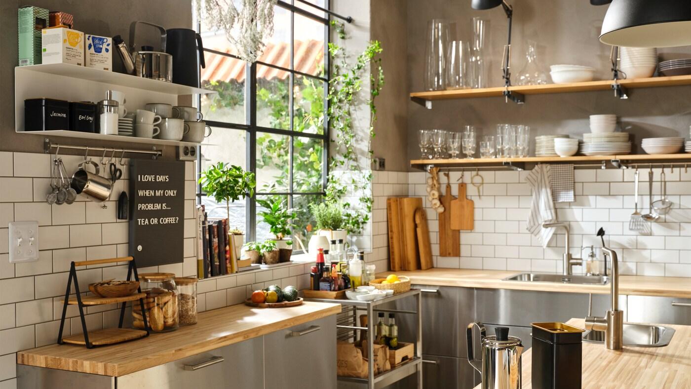 Stort, halvprofessionelt køkken med bordplader af træ, fronter af rustfrit stål og åbne hylder til porcelæn.