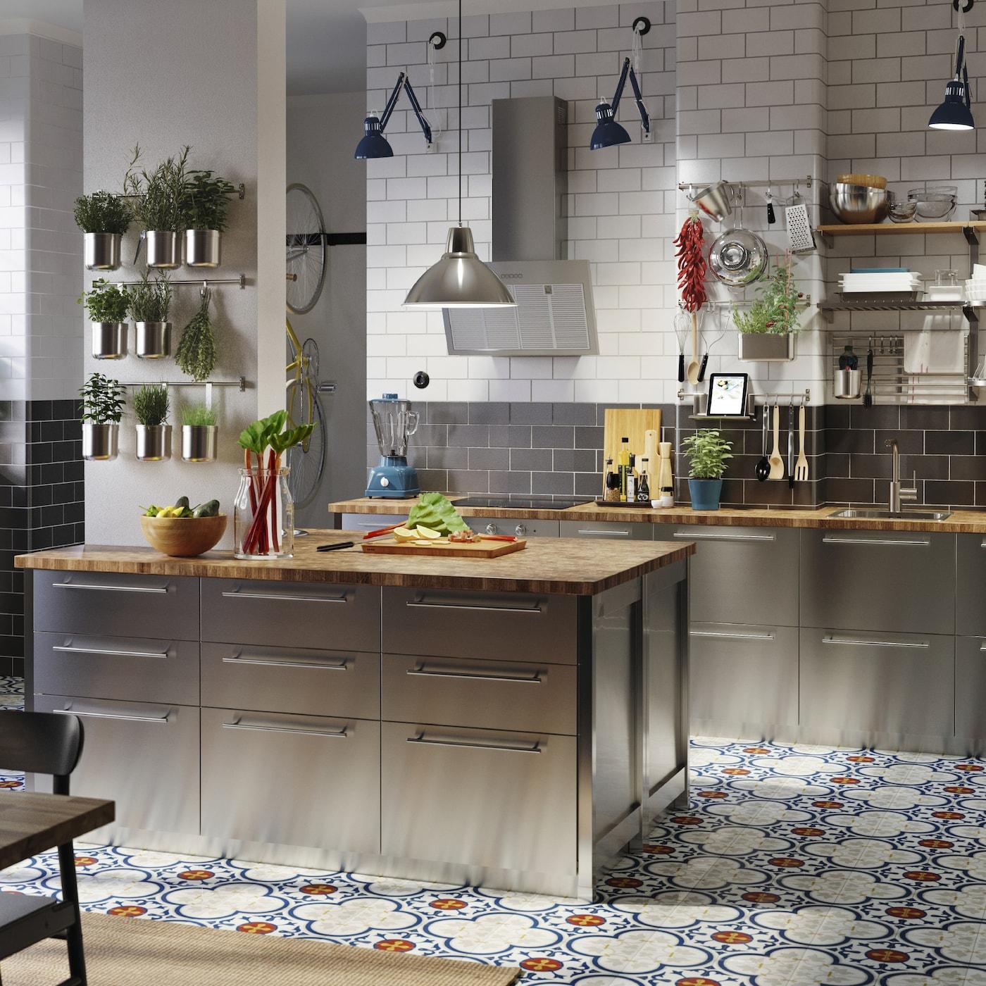 Stort kök med fronter i rostfritt stål, bänkskivor i ek/faner, blå arbetslampor i industriell stil och örtkryddor i burkar.