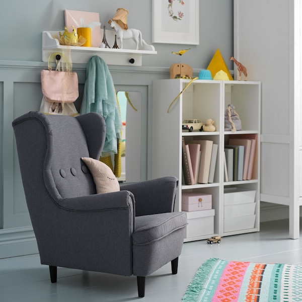STRANDMON dečja fotelja u tamnosivoj nijansi se nalazi pored belih spojenih polica, na kojoj su knjige i igračke.