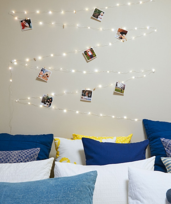 String lights and photos zig-zagged on the wall above a bed filled with cushions.
