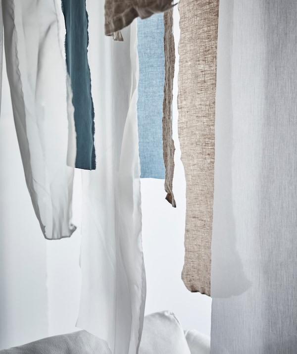 Strips of hanging textile fabric in front of a window.
