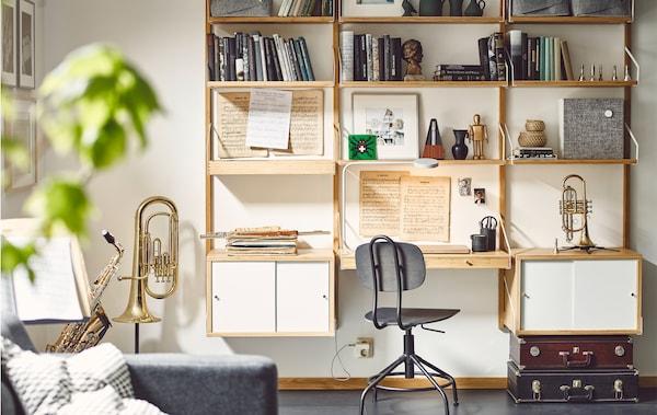 Strumenti musicali, spartiti e libri su una combinazione da parete con scrivania e mobili con ante scorrevoli - IKEA