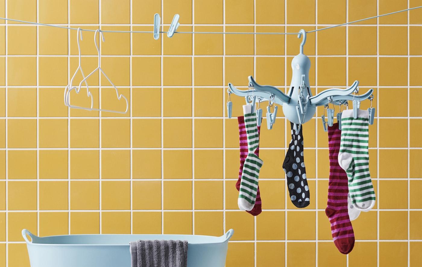 Strumpor på en blå hängtork, klädnypor och galgar på en tvättlina med en gulkaklad vägg i bakgrunden.