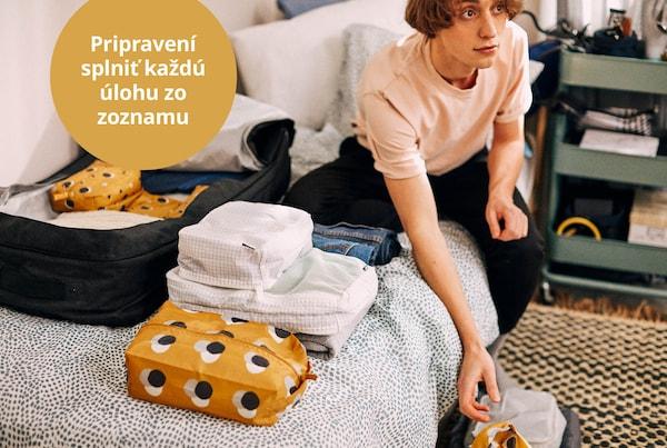 Študent sedí na posteli a balí sa na internát.