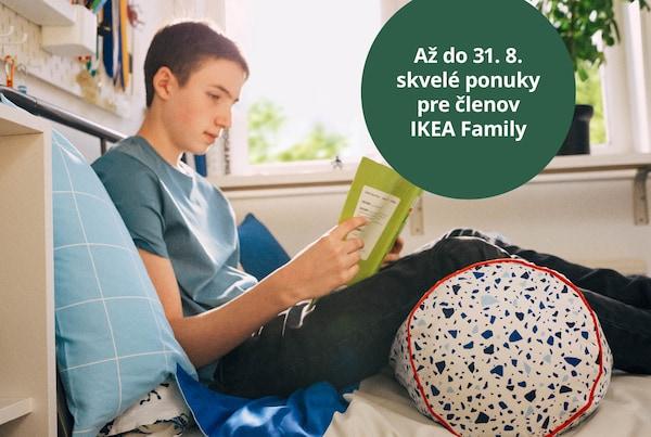 Študent sedí na posteli a číta, pričom sa opiera o vankúš s nohami podloženými vankúšom MÖJLIGHET.