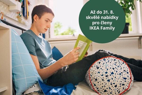 Student sedí na posteli, opírá se o polštář a pod nohama má polštář MÖJLIGHET jako podporu.