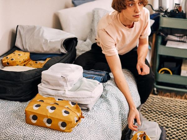 Student siedzi na swoim łóżku, na którym rozłożone są poukładane w torbach RENSARE rzeczy, które zabiera ze sobą na studia.