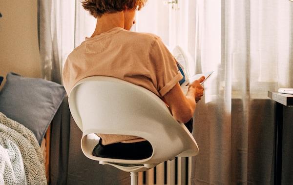Student uczy się, siedząc na krześle obrotowym przed oknem, z nogami opartymi na kaloryferze.