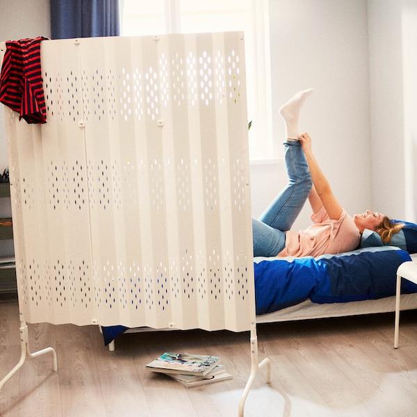 Študentka sa oblieka na posteli a je čiastočne zakrytá paravánom SAMMANKOPPLA.