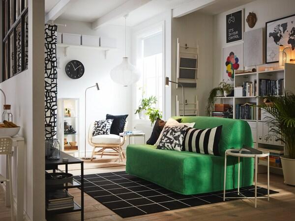 Studio avec canapé convertible 2 places VANSBRO en vert vif, textiles en noir et blanc, bibliothèques blanches et fauteuil.