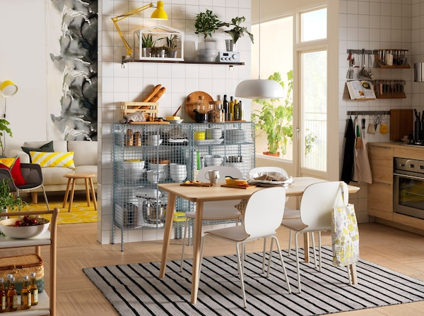 Studio blanc, noir et jaune avec table en bois et chaises blanches.