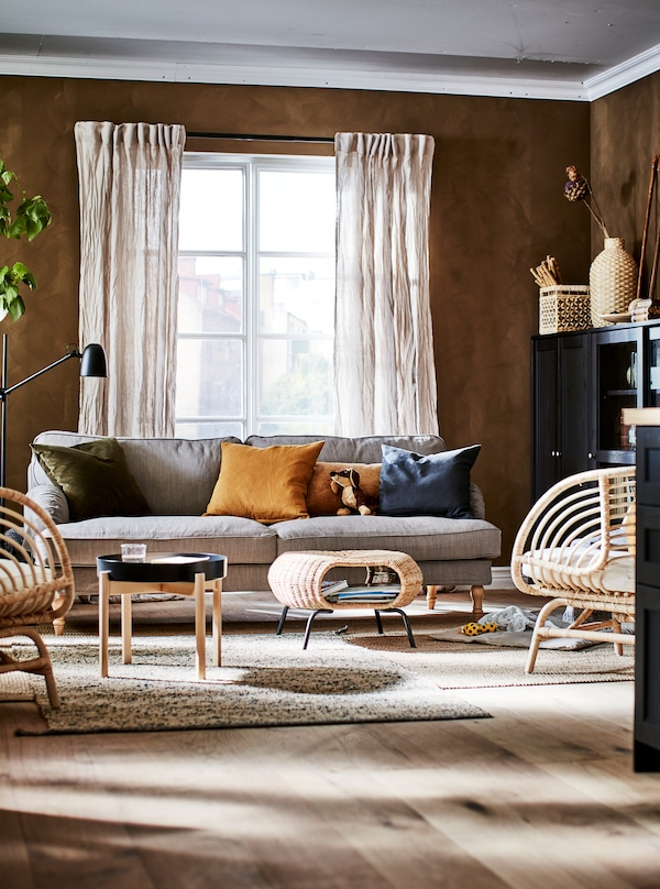 Stue i jordfarver med dekorationer, opbevaring, BUSKBO lænestole, en sofa, et sofabord og en taburet.