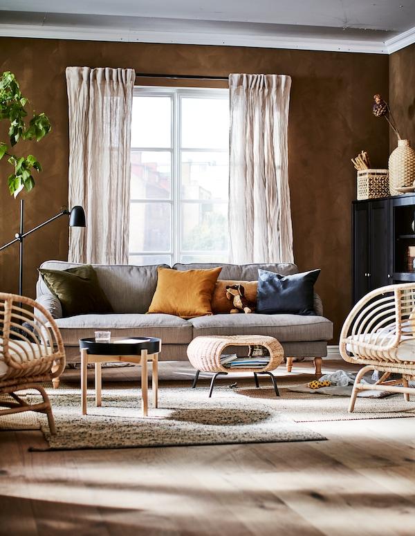 Stue i jordfarver med dekorationer, opbevaring, siddepladser, et sofabord, en puf og en plante.