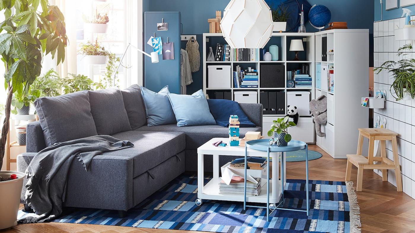 Stue med en mørkegrå hjørnesovesofa, et tæppe med et blåt mønster og en fritstående reol med plads bagved.