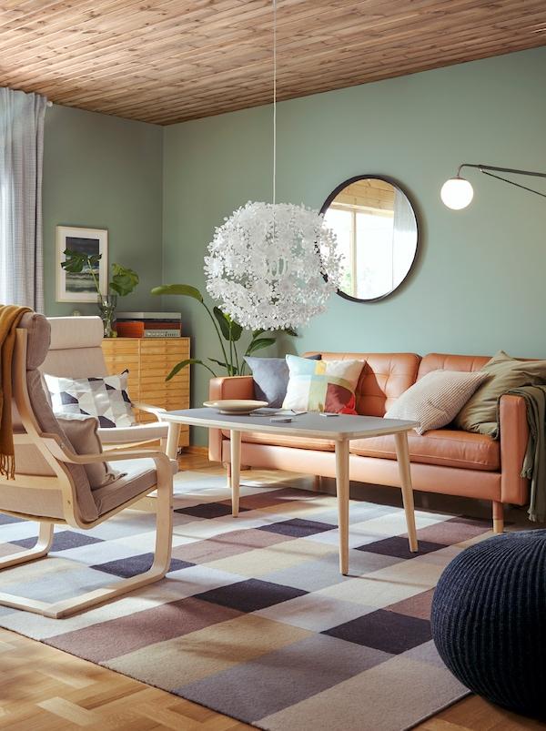 Stue med en sofa, et sofabord og 2 lysebrune og hvide POÄNG lænestole med stel af formspændt, lyst træ.