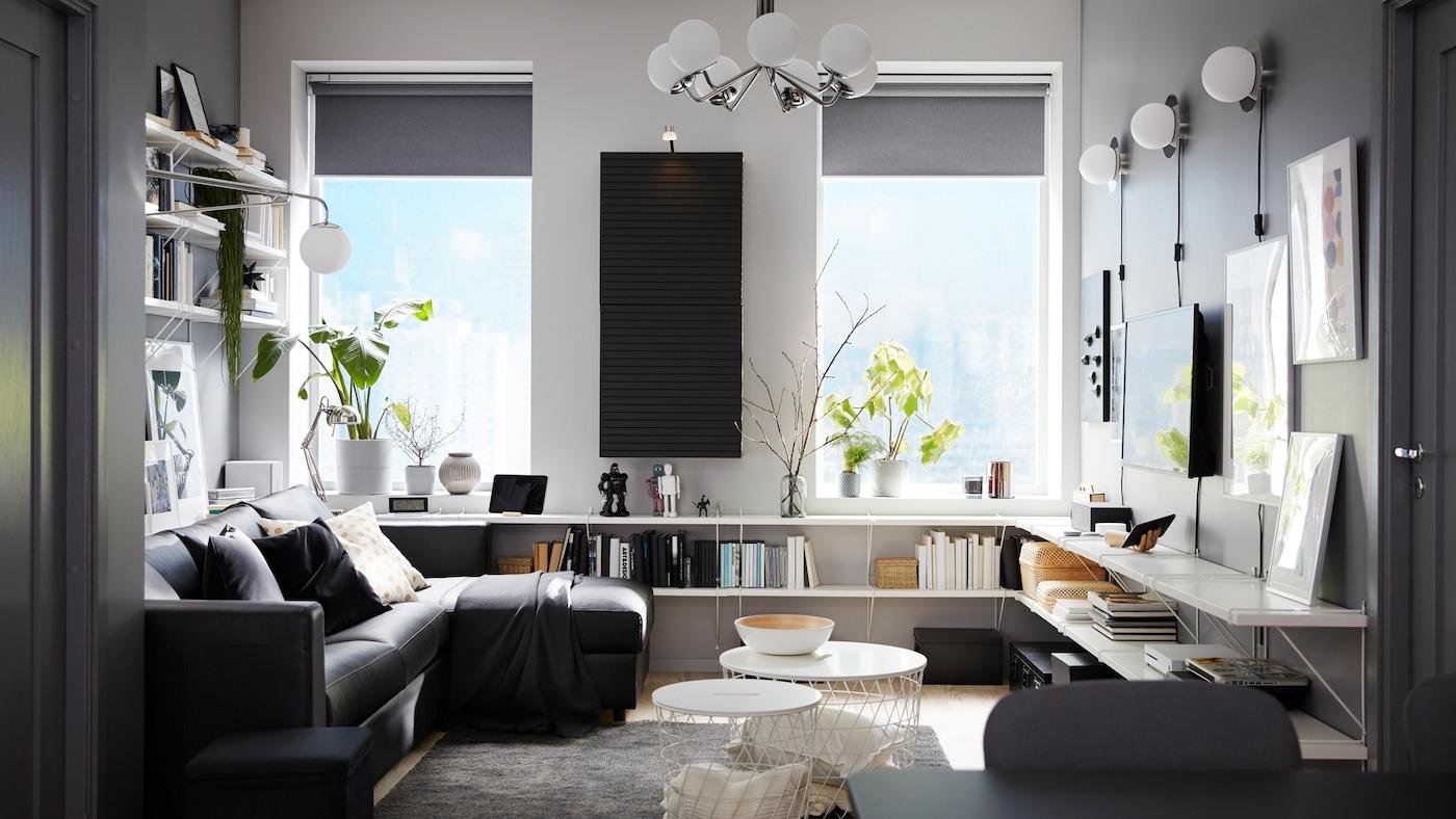 Stue med en sort sovesofa med chaiselong, hvide hylder, et vægmonteret skab i antracit og et mørkegråt tæppe.