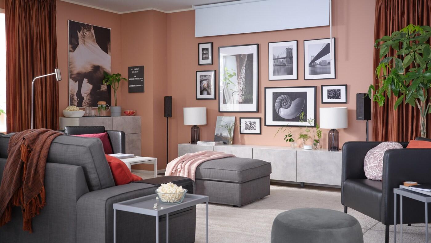 Stue med en væg med indrammet kunst, et mørklægningsrullegardin, lysdæmpende gardiner og en 3-pers. sofa.