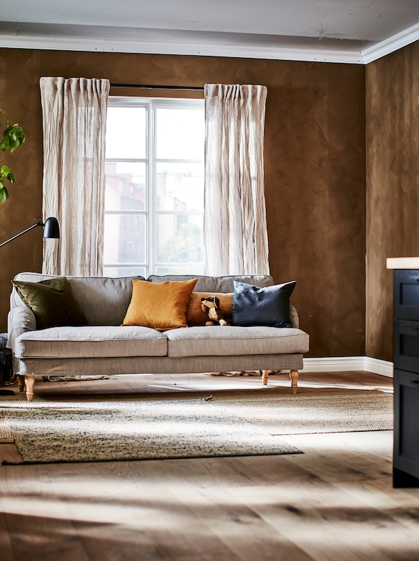Stue med franske døre, gardiner af krøllet hør, en sofa med puder, en SKURUP lampe og tæpper af naturmaterialer.