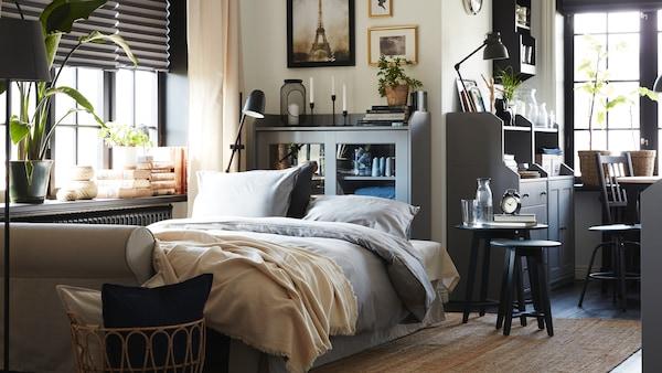 Stue med lys beige sovesofa, juteteppe, stol i rotting og bambus og to skap og en kommode i grått.